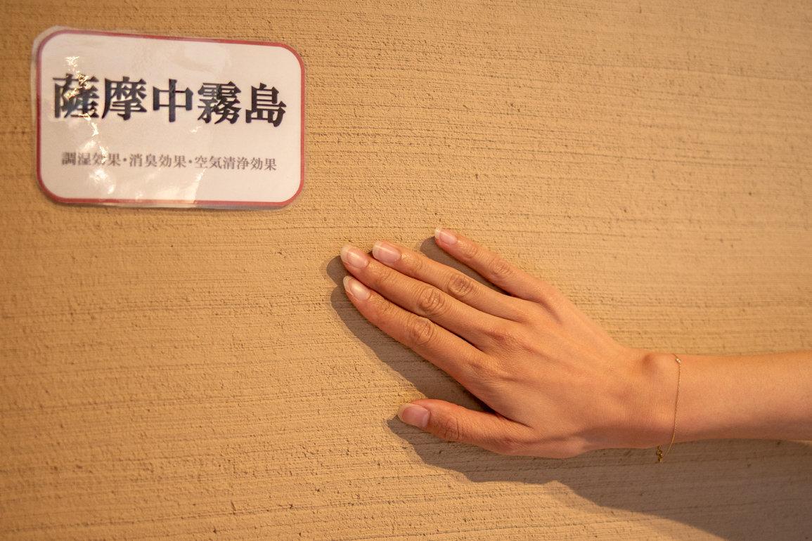 納得住宅狭山のモデルハウスで薩摩中霧島の壁を触って体感している