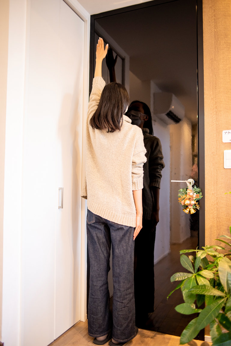 身長170cmのスタッフが手を伸ばしてドアの高さを確認している